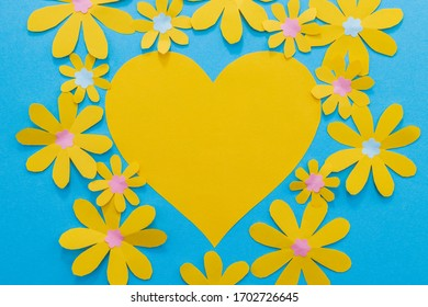 Mothers day concept with a yellow paper heart surrounded by yellow paper flowers. On a bright blue background. Room for copy.