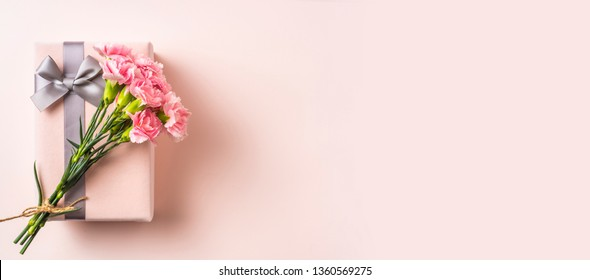 mothers day design concept - top view of a bunch of carnation, gift box on pink background for wedding and valentines day with copy space for mock up