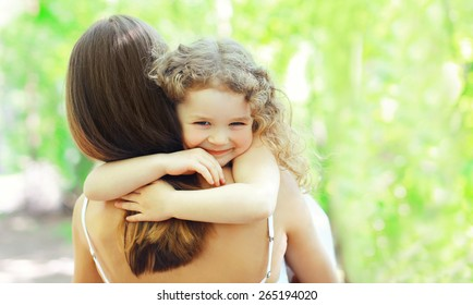 Mother's day, family, childhood and people concept - happy daughter hugging mother in warm sunny summer day on the nature