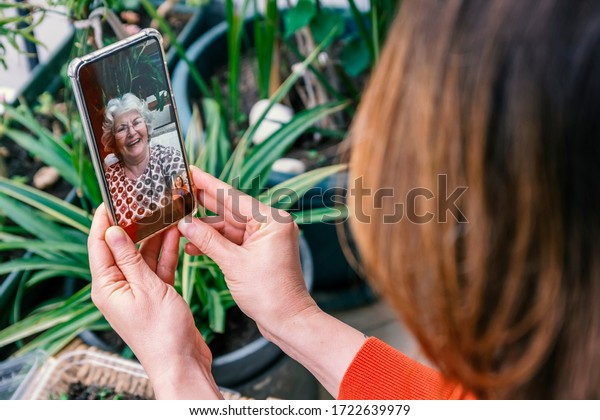 Mother's day lockdown concept: Mother and child laughing during online video call, celebrating this special day. Woman with white hair and glasses smiles into camera. Green leaves in background