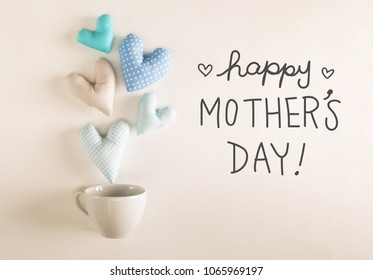 Mother's Day message with blue heart cushions coming out of a coffee cup