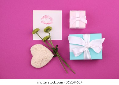 Mothers day message with gift box, wool heart shape and flowers on pink background.