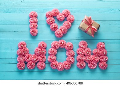 Mothers day message of pink paper flowers over blue wooden board. Happy mother's day concept.