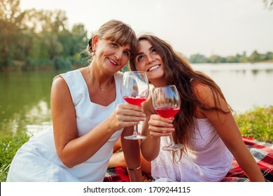Mother's day. Mother drinking wine with her adult daughter in spring park. Family having picnic outdoors.