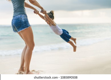Mother's Day. Mother turns her daughter by the arms. Happy Mom and happy child traveling to Asia, at the beach. Traveling with your family, child. Important to spend enough time with your kids.