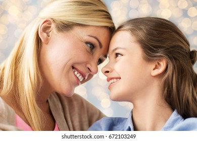 mothers day, people and family concept - happy smiling girl with mother over lights background