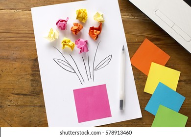 Mother's day present: white office sheet of paper with colorful small papers, representations of flowers for holidays