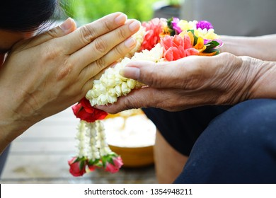 Mother's Day or Songkran Festival theme woman putting the hands together in sign of pay respects after giving Thai traditional jasmine garland to parents or revered elders, elderly people in family.