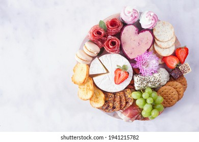 Mother's Day theme charcuterie board against a white marble background. Assortment of cheese, meat, fruit and sweet appetizers. Top down view.