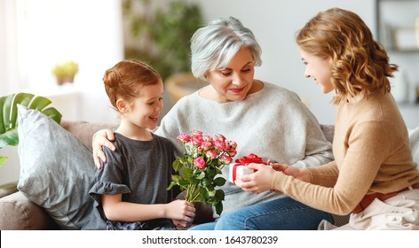 mother's day! three generations of a loving family mother, grandmother and daughter congratulate on the holiday, give flowers
