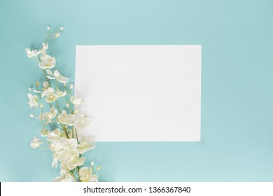 Mothers day or wedding floral card with paper note and white flowers over a blue background shot from above. Flat lay.