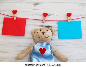 Mother's day. Women's day. Valentine's day, Birthday background. envelope with heart peg and little bear on the wooden white background .