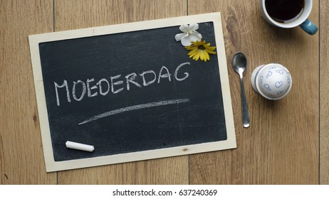 Mother's day written in Dutch on a chalkboard next to a egg and flowers