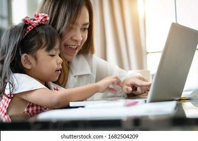 Mother's Day.Little girl looking at laptop computer with her mom.Concept family happy. stay home