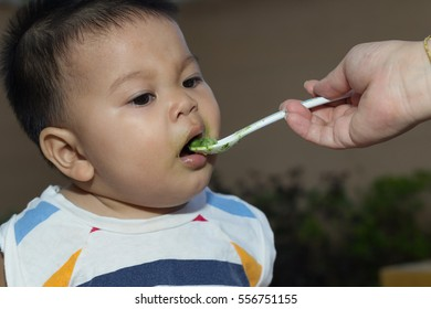mother's hand feeding a young child from a white plastic spoon.