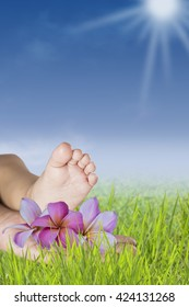 mothers hand holding babies little feet, relaxation in touch with nature - background
