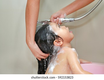 Mother's hand pours water from shower to wash little girl's hair