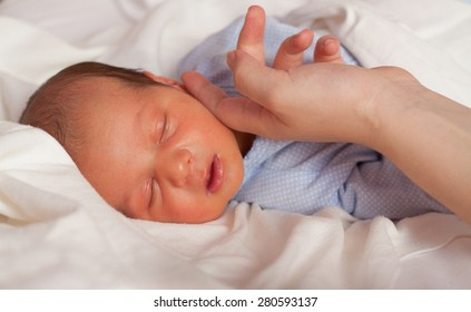 Mother's hand touching sleeping newborn baby