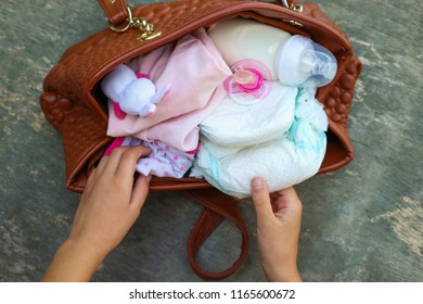 Mother's handbag with items to care for child. Women's hands take things out of bag.