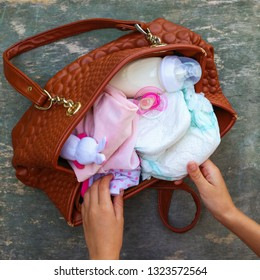 Mother's handbag with items to care for child on old wooden background. Women's hands take things out of bag.