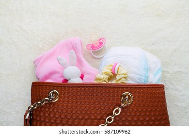 Mother's handbag with items to care for child on white background. Top view.