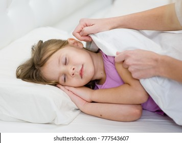 Mother's hands covering little sleeping girl with blanket
