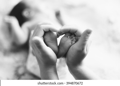 Mother's hands holding the little feet of a newborn baby (black-and-white photo)