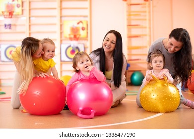 Mothers with happy babies doing exercises with gymnastic ball in gym. Concept of caring for the baby's health.