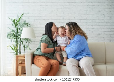 Mothers kissing their happy laughing child on both cheecks