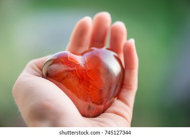 Mothers love. Woman's hands holding heart shaped gemstone. Healthy lifestyle concept - taking care of heart health. Healing crystals with powerful energy