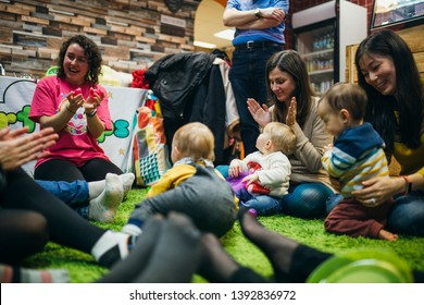 Mothers and their baby children are in a sensory play group. They are singing and dancing together in a circle on the floor.