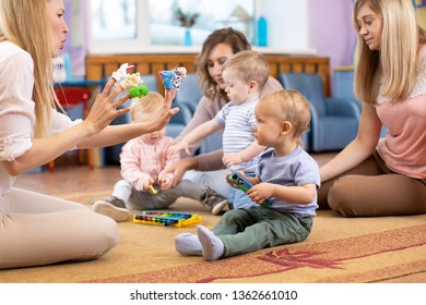 Mothers and their children together in club. Babies playing with musical toys
