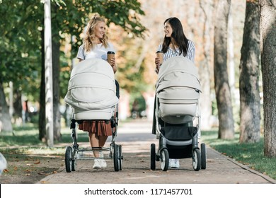 mothers walking with baby strollers and coffee to go in park and looking at each other