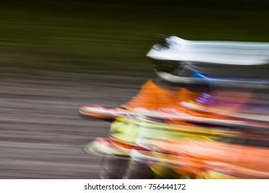 Motion blur artistic image of a motocross rider speeding down the track.