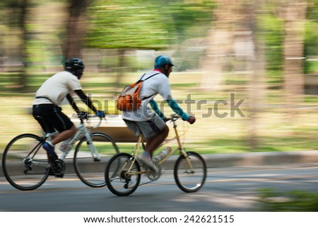 Motion blur of a bike rider in public park