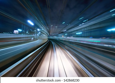 Motion blur of a city and tunnel from inside a moving monorail in Tokyo.