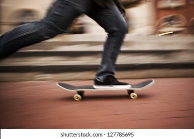 Motion blur of fast skateboarder feet moving