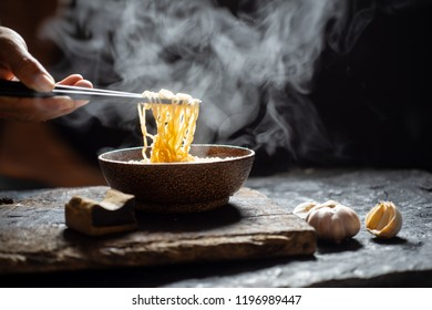 Motion blur Hand uses chopsticks to tasty noodles with steam and smoke in bowl on wooden background, selective focus. Asian meal on a table, junk food concept