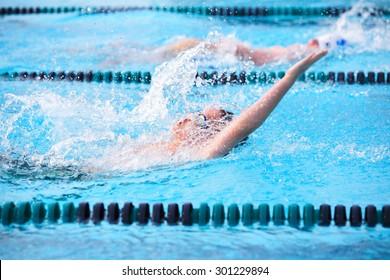 Motion blur image of a boy swimming backstroke in a race.