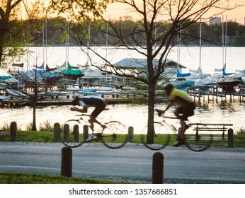 Motion Blur Image of Cyclists Cycling at White Rock Lake Park In Dallas Texas During Warm Golden Hour Sunset in Background