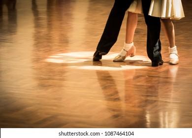 Motion blur of Junior couple dancers in a dance spotlight on the floor, Juvennile level in  Grand Slam Standard Dance.
