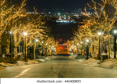 Motion blur of Light View on trees, see the yacht from top hill on road direct to Hakodate Harbor. The wind and snow storm are coming at Motomachi Area, Hokkaido, Japan.