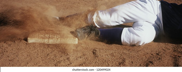 Motion blur low section show of a young baseball player sliding towards base on field