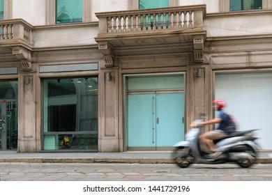Motion blur of man moving fast driving motorbike on Italian street