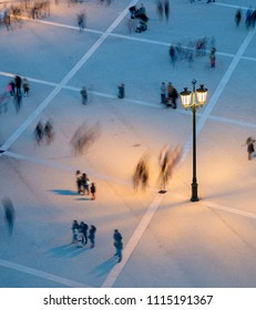 Motion blur of many people on a public square at twilight. View from above