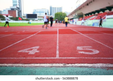 Motion Blur on Red running track in stadium,group of male and female who love to workout