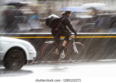 motion blur picture of a cyclist in the traffic of a city street at heavy rain