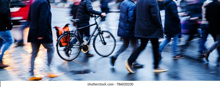 motion blur picture of people and bicycle crossing a city street at dusk