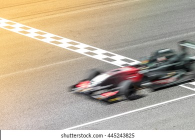 Motion blur, Race car racing on race track with start and finish line.