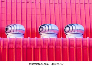 Motion blur of rusty air ventilator on the red roofof factory